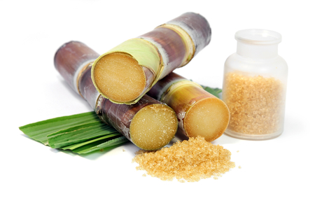 Sugarcane with leaves and a bottle of granulated sugar on white background.