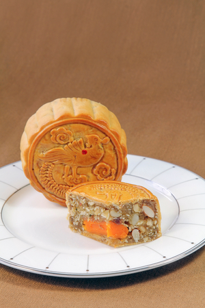 Fruits and Nuts Mooncake with Egg on a white dish, Chinese sweet. Stock Photo