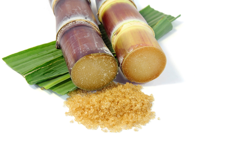 sugarcane: Granulated brown sugar with sugarcane and leaves on white background.