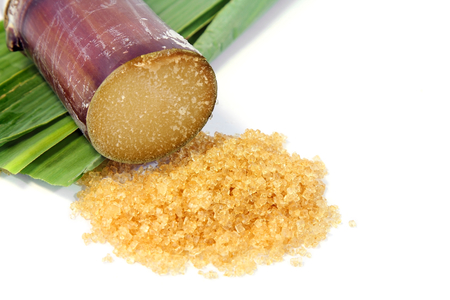 Granulated brown sugar with sugarcane and leaves on white background.