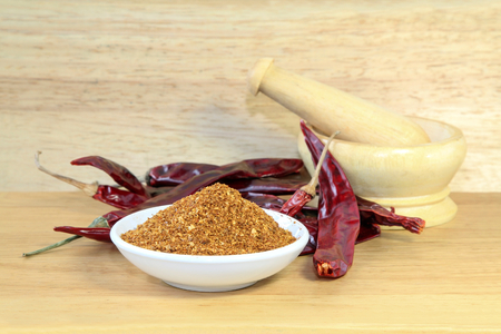 Chili powder, dried red chili pepper and mortar on wooden background, Food ingredient.