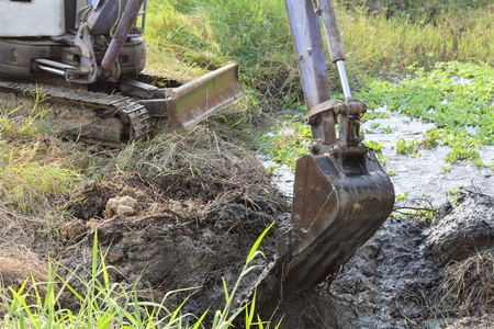 Dirty bucket of backhoe digging  mud and weed in a canal.