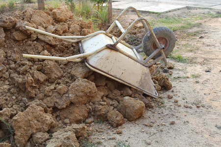 Old rusty wheelbarrow upside down on a heap of soil in a building site, construction area.