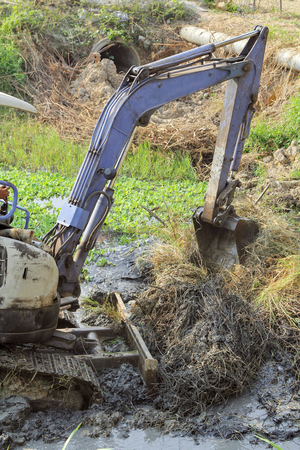 Working excavator backhoe opening shovel bucket to cleans up mud and grass in a riverbank cover with weed.