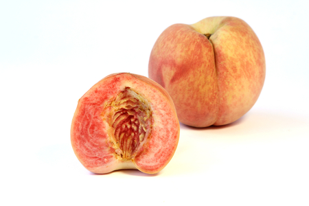 Ripe Japanese white peach fruits with sliced  on white background. Stock Photo