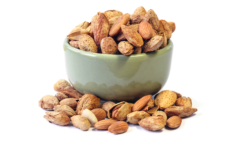 Roasted Almond nut in shell and shelled on a bowl isolated on white background Stock Photo