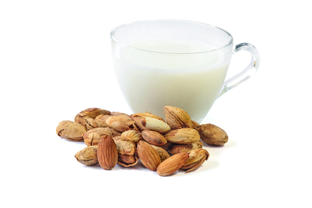 Roasted Almond nut in shell and shelled and a cup of almonds milk isolated on white background