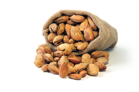 Group of Almond in shell and shelled in burlap sack isolated on white background ,nut, vegetarians food. Stock Photo