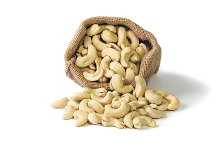 Cashew nuts in burlap sack isolated on white background, Food. Stock Photo