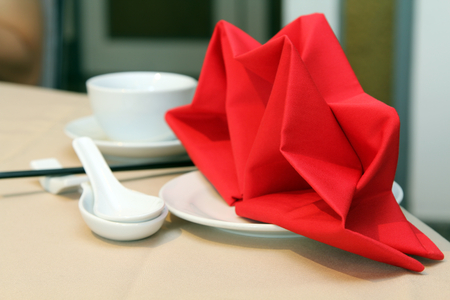 Red linen napkin with spoon and  chopsticks  on table set in Chinese style.