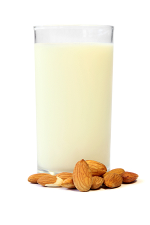 Roasted Almond nut and a glass of almonds milk isolated on white background.
