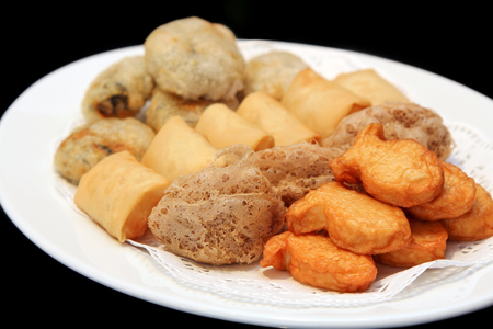 Deep Fried Fish Bean Cake, Deep Fried Mash Taro, Deep Fried Spring Roll, Deep Fried  Chinese Chives in a white dish, Dim Sum, Chinese cuisine, Food, black background. Stock Photo