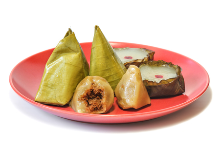 Stuffed Dough Pyramid Dessert (Ka-Nhom-Tian) wrapped with banana leaf in pyramid shape and Nian gao (Chinese new years rice cake) for celebrate Chinese new year festival on white background, dessert.