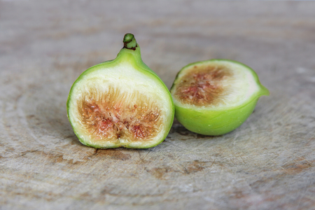 cut through: Conadria figs cut through to show the flesh and seeds on wooden background.
