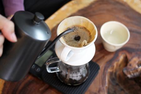 Hand Drip Coffee, Barista derramando água quente sobre o pó de café moído torrado, fazendo café com gotejamento.