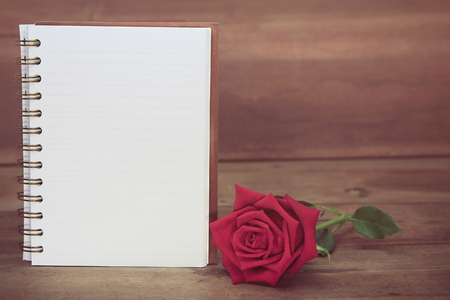 Rode rozen en een wit boek op houten achtergrond, exemplaarruimte voor tekst, Uitstekende toon. Stockfoto - 89446559