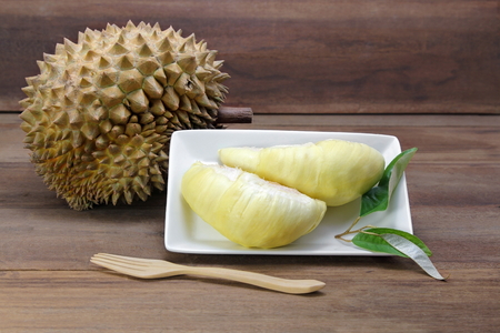 Durian fruits and yellow flesh durian on white dish with durian leaf, wooden background, Asia fruits, The durian is distinctive for its large size, strong odour, and formidable thorn-covered rind.