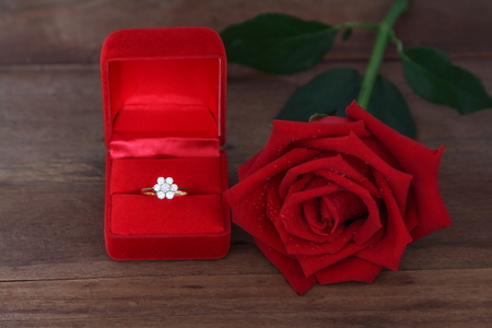 Diamond ring in red box with big red roses  on wooden background, Valentine, love and marriage concept. Stockfoto