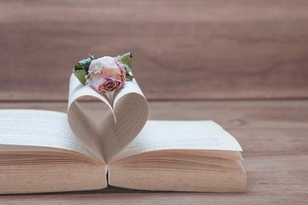 Droge roze nam op het oude Hart gevormde boek, roze tonen, Valentine-concept toe. Stockfoto - 93642740