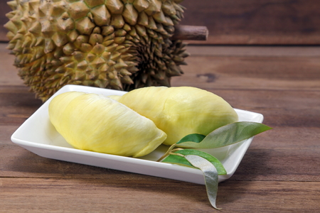 Durian and Durian leaf on wooden background, exotic fruits, Thailand.