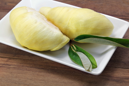 Ripe yellow flesh of Durian on white plate and durian leaf on wooden background, asia fruits, Thailand.