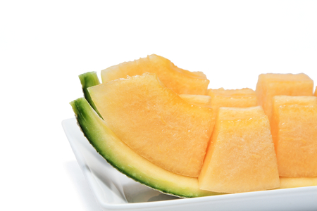 Close up of sliced melon in pieces on a white plate isolated on white background. Stockfoto