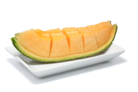 Sliced melon in pieces on a white plate .