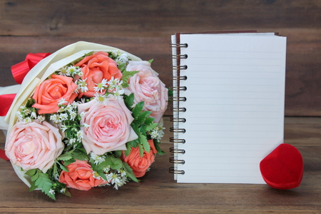 Wedding bouquet from pink and orange roses, red ring box and a white book on wooden background, copy space for text. Stockfoto