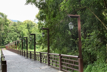 The bridge across the River to the forest with hanging lamps electrical poles.  landscape.