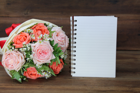 Beautiful bouquet from pink and orange roses and a white book on wooden background for congratulations, copy space for text. Stockfoto