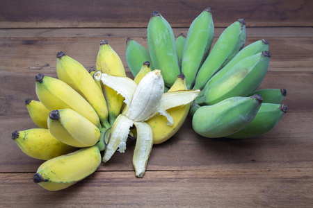 Ripe yellow bananas peeled to show white flesh, raw green bananas on wooden background. Tropical Fruit. Stockfoto
