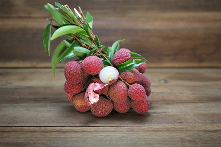Fresh bunch of lychee fruit (Litchi chinensis) peeled to show the flesh white on wooden background, Southeast Asia tropical juicy fruit, Sweet and sour taste. Stockfoto