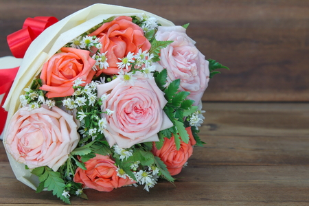 Beautiful bouquet from pink and orange roses on wooden background for congratulations, copy space for text.