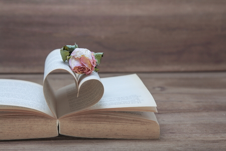 Single dried pink rose on the old Heart shaped book on wood background, pink tones, copy space for text.
