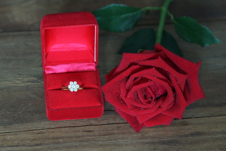 Diamond ring in red box with big red roses Hybrid Tea on wooden background, Valentine, love and marriage concept. Stockfoto