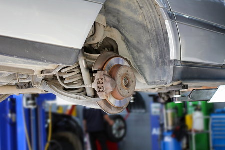 Maintenance of Brake Disc of the car lifted in air at car service.