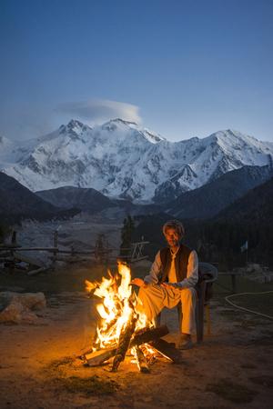 Fairy Meadows, Pakistan - October 4, 2017: A Pakistani man was sitting near the bonfire at Fairy Meadows, Pakistan. The background is Nanga Parbat mountain. Editorial
