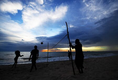 Silhouette, unidentify people, sport activity from a beach of Lanta island, Krabi province, south of Thailand at sunset and twilight time.