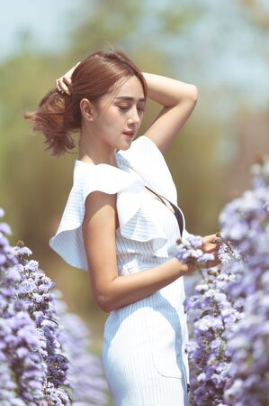 Beautiful Thai lady is walking around in a beautiful flower garden. She is wearing a sexy white dress. She has brown hair and eyes.