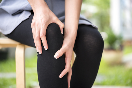 Health care concept, Hands suffering from pain in knee Stock Photo