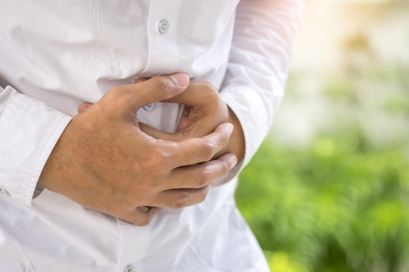 Gastritis, Stomach pain, reflux acids, Man suffers painful abdomen injury and holds painful area with hands.
