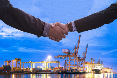 Business Collaboration, Businessman shake hands with transportation logistic import export background night city town. Stock Photo