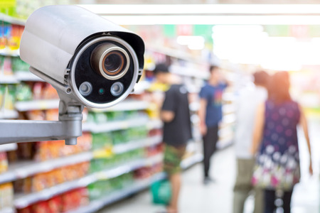 Security CCTV camera in supermarket with people shopping in supermarket blur background