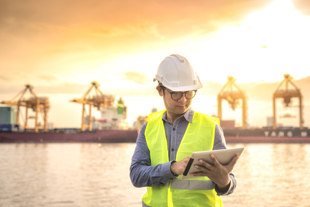 Engineer checking scheduled ship with shipping application on digital tablet