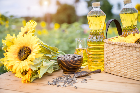 Organic sunflower oil in the glass jar with sunflower seeds, sunflowers on the table at sunflower farm.