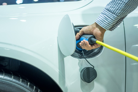 Hand plug the charger access to vehicle electrification. Hybrid car and technology automotive concept