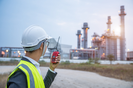 Electrical engineer working at power plant with walkie-talkie or radio communication, Power Industrial concept. Standard-Bild