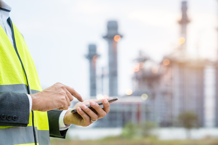 Electrical engineer use cell phone at power plant, Communication concept.