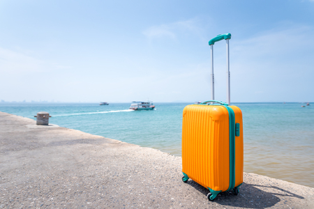 Big orange travel bag and the sea beautiful blue sky with boat background, Vacation concept.