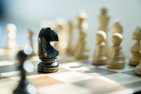 Wooden chess pieces on a chessboard, leadership strategy and business plan concept.